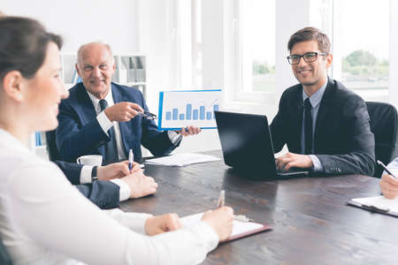 chairman: Smiling office workers of different ages during a meeting, showing graphs and taking notes