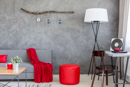 pouffe: Contemporary living room with a grey stucco wall and red decorative items