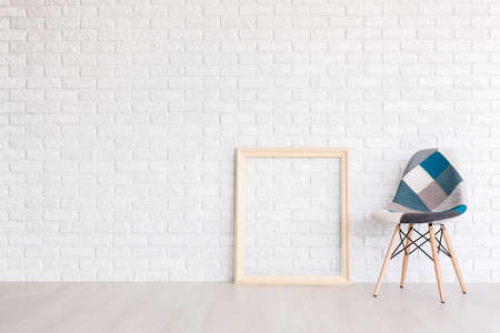 interior designer: White post industrial interior with a wooden picture frame and a designer patchwork chair