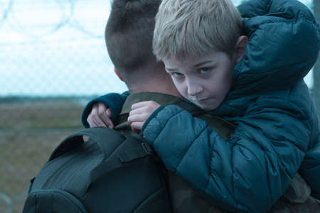 miserable: Miserable little boy hugging his soldier dad before his departure Stock Photo