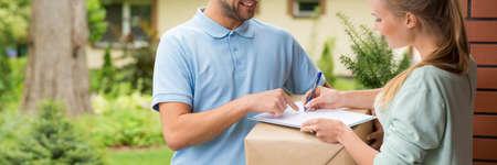 confirmacion: Mujer joven que firma una confirmación de entrega en frente de su casa