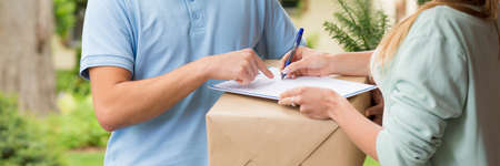 Close-up panorama of a courier delivering a large package to a recipient