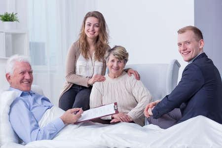 Geschossen von einem älteren Mann, der ungefähr ist, sein letztes Testament zu unterzeichnen, das auf ein Krankenhausbett legt, das von seiner Familie umgeben wird