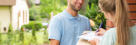 Young woman receiving a package from a smiling courier Stock Photo