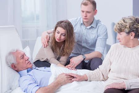 Disparo de un hombre mayor enfermo rodeado de su familia apoyándolo