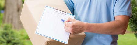 confirmacion: Primer plano panorama de un Mensajero que sostiene un paquete grande y una hoja de confirmación