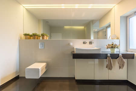 elegant design: Light and spacious high gloss bathroom with large mirror and modern furniture