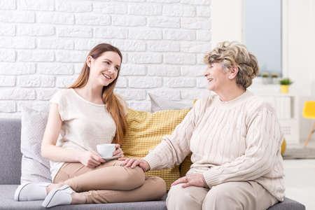 apoyo familiar: Alegre altos dama hablando con su nieta en un sofá gris