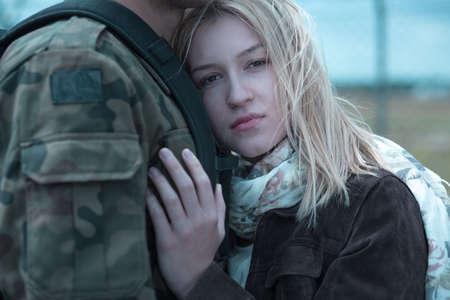 Close-up van een jonge vrouw droevig knuffelen haar vriendje soldaat