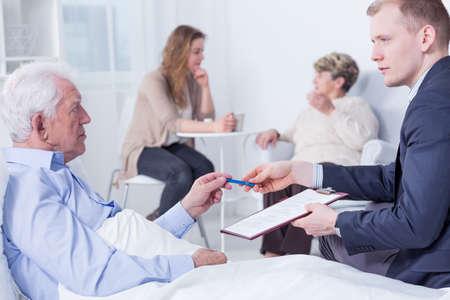 Geschossen von einem älteren Mann über seinen letzten Willen auf einem Krankenhausbett zu unterzeichnen mit seinem Anwalt neben ihm saß