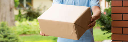 Close-up panorama of a large wrapped box in the hands of a courier