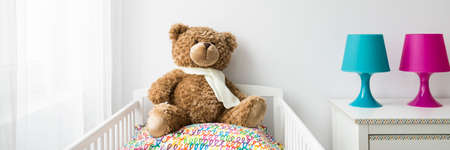 baby toys: White baby bedroom with a crib and a teddy bear