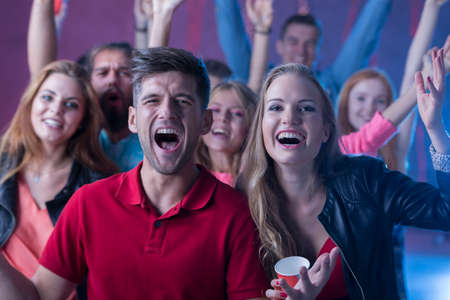 Shot of a group of young people screaming and singing at a party Stock Photo