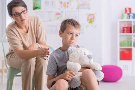psychologists: Shot of a sad boy holding a teddy bear in psychologists office Stock Photo