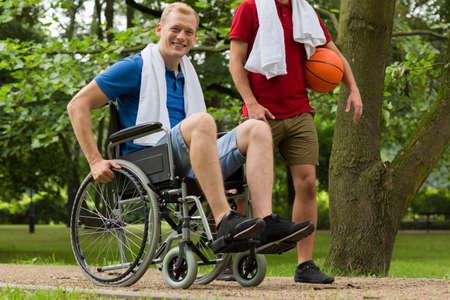 Shot van een jonge man met behulp van rolstoel lachend naar de camera in een park