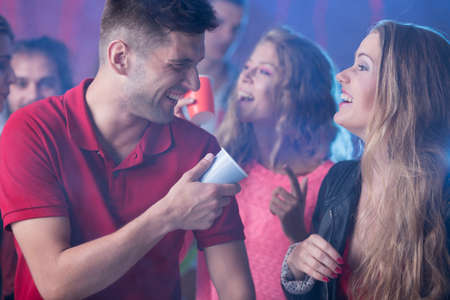 nightclub crowd: Shot of a young men talking to his girlfriend during a party