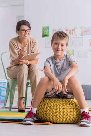 Shot of a smiling young boy sitting on a pouf in a psychologists office