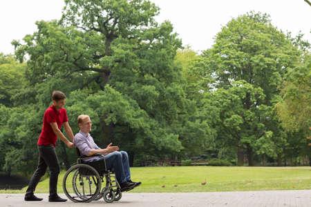 caminar: Disparo de un hombre joven y su amigo en una silla de ruedas que tiene una caminata en un parque