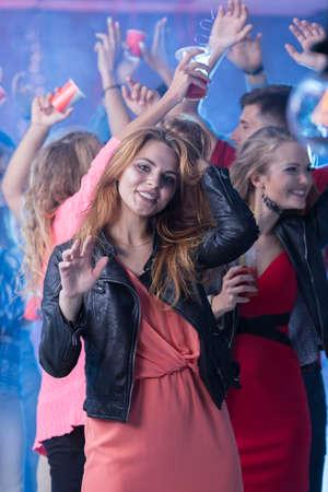 Tir d'une jolie jeune femme qui danse à une fête
