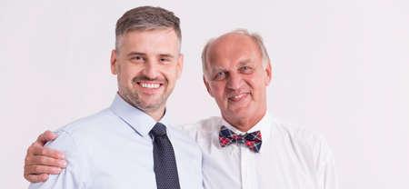 senior adult man: Senior man embracing his smiling adult son, light background, panorama