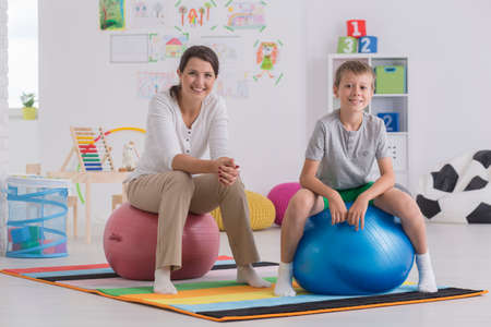 posture correction: Shot of a young woman and a little boy sitting on exercise balls in a room