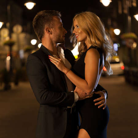dressed up: A dressed up couple embracing in a city at night