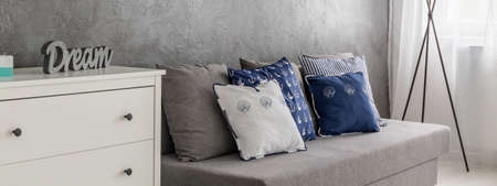 interior decor: Simple grey sofa with marine style decorative pillows