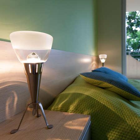 bedside: Bright green bedroom with modern bedside lamps