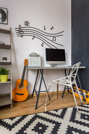 wall decoration: Modern home office with small desk, crystal chair, music wall decor and pattern carpet