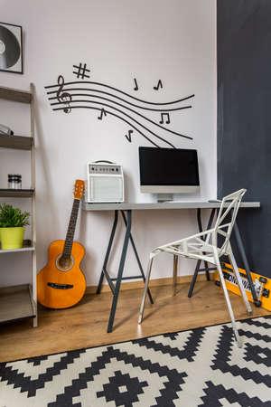 Moderne Home-Office mit kleinen Schreibtisch, Kristall-Stuhl, Musikwanddekor und Muster Teppich Standard-Bild - 63928462