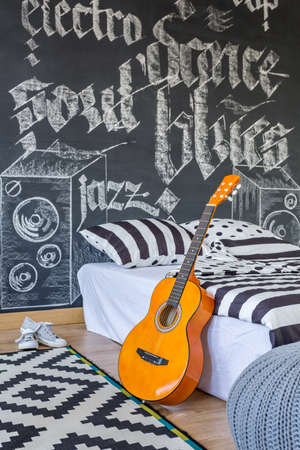 wall decoration: Black and white creative bedroom with a blackboard wall, a guitar standing beside a bed