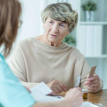 Mujer mayor hablando con un trabajador social en casa Foto de archivo - 63928749