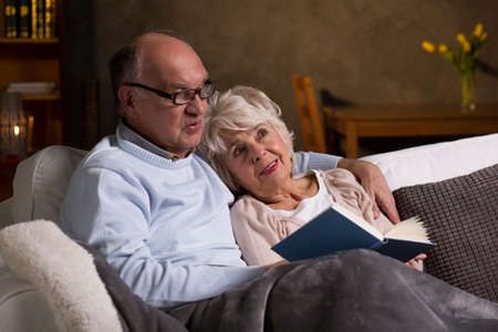 elderly adults: Two retired people relaxing on the couch reading the book