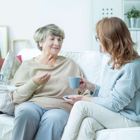 elderly adults: Mother and daughter are drinking coffee together