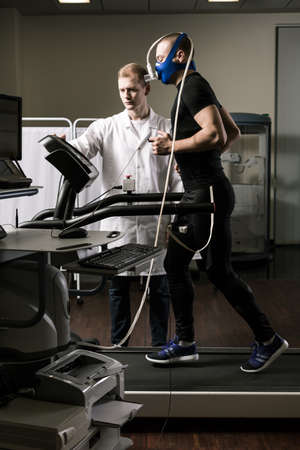 Shot of an athlete wearing an oxygen mask and running on a treadmill during medical examination Stock Photo