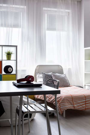 cosy: Minimalistic desk in bright bedroom with the cosy bed behind Stock Photo