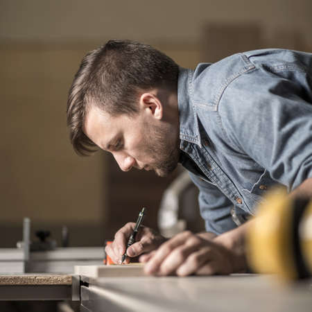Vertical photo of young carpenter making marks for cutting Stock Photo