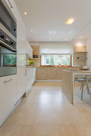 open plan: Open plan kitchen area surrounded by cupboards with oven and fridge, with table and minimalistic chair and with the window