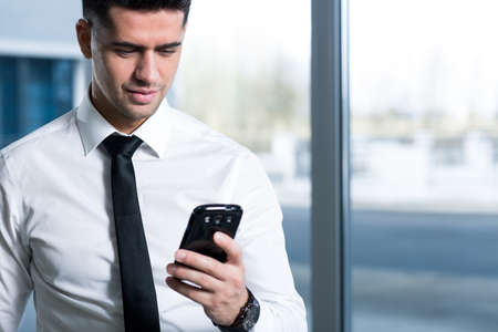 clothed: Smartly clothed businessman looking at his mobile phone