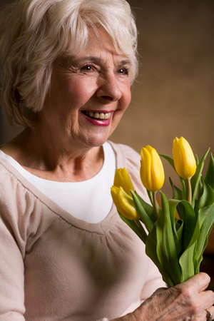 grey haired: Grey haired elderly woman holding yellow tulips