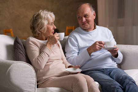 gente sentada: Las personas mayores que se sientan en el sofá y bebiendo café