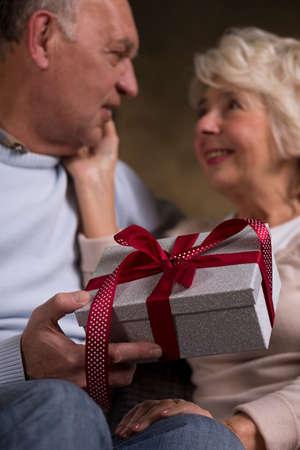 agradecimiento: Elderly people holding gift in their hands Foto de archivo