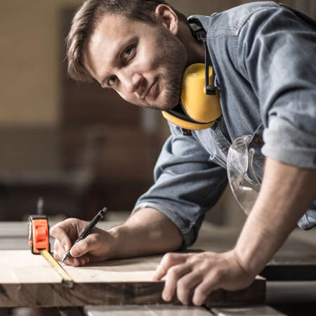 labouring: Photo of handsome carpenter measuring wooden board