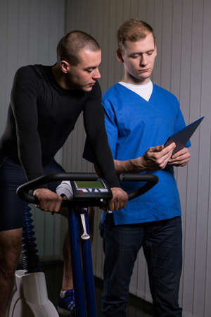 Shot of a young man sitting on a stationary bike and a medic showing him his results
