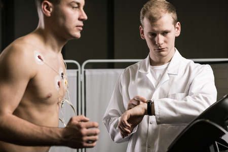 Shot of a doctor supervising his patient on a treadmill during his cardiac stress test Stock Photo