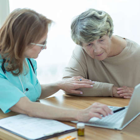 patient in hospital: Doctor and patient looking at laptops screen Stock Photo