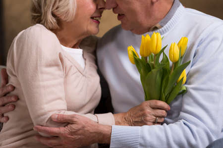 grabbing: Couple of senior citizens holding each other and grabbing tulips Stock Photo