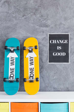 commode: Two skateboards standing on a commode close to the black poster
