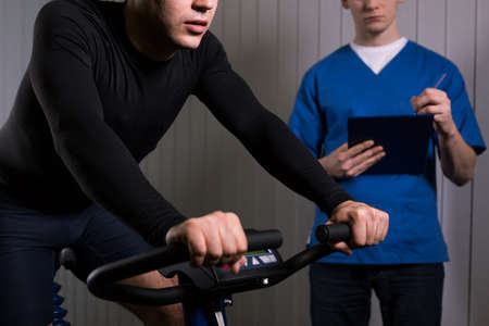 stationary: Cropped shot of a patient riding a stationary bike and medic writing on his chart Stock Photo