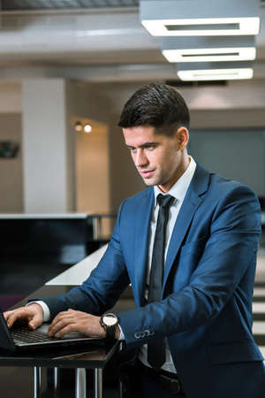 professionalist: Young and handsome businesmann typing on his laptop in an work office Stock Photo